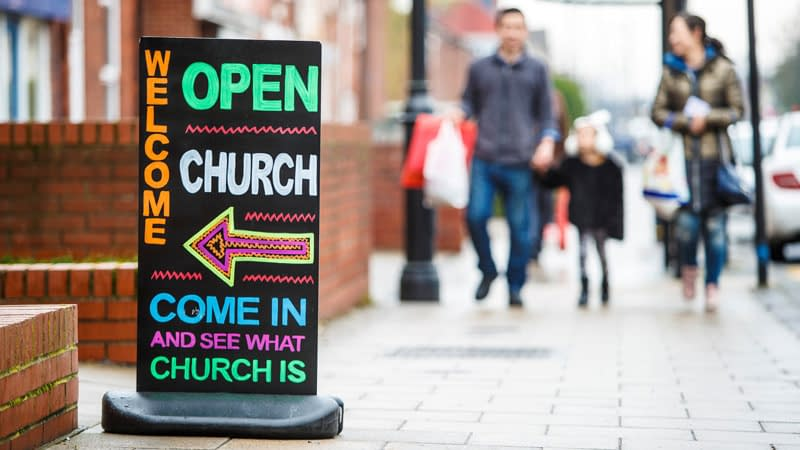 Colourful street sign point to church