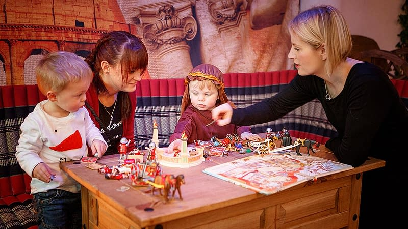 Adults and children play with model soldiers