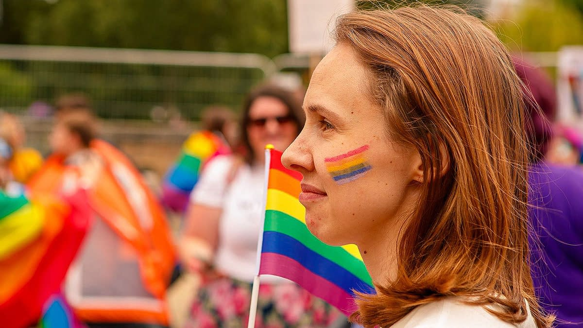 Smiling young woman with a rainbow painted on her cheek