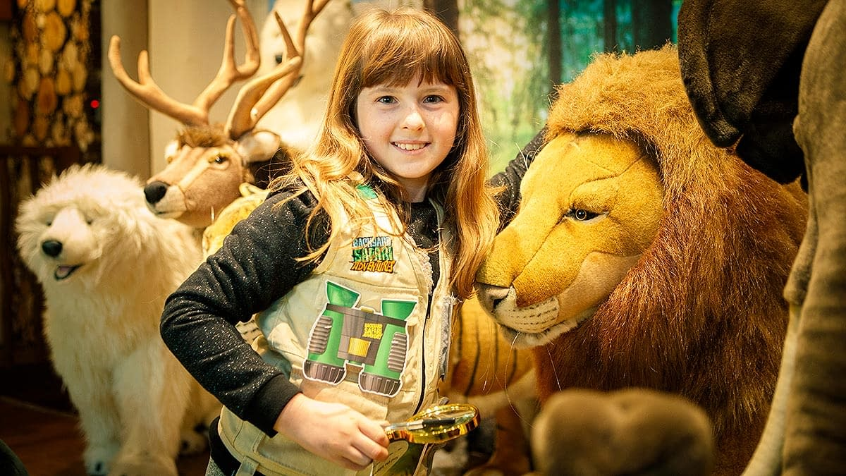 A young girls next to a life size lion