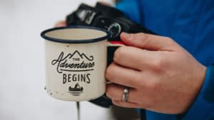 Person holding white enamel mug with slogan on