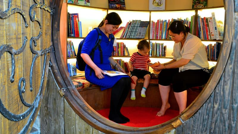 Two adults and a young child enjoy looking at books