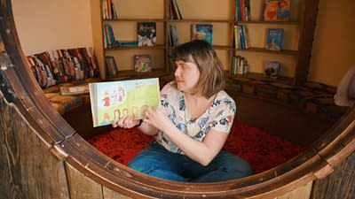 The storyteller turns a page of the book