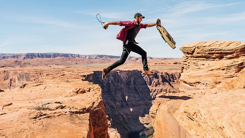 Man leaping in faith across ravine
