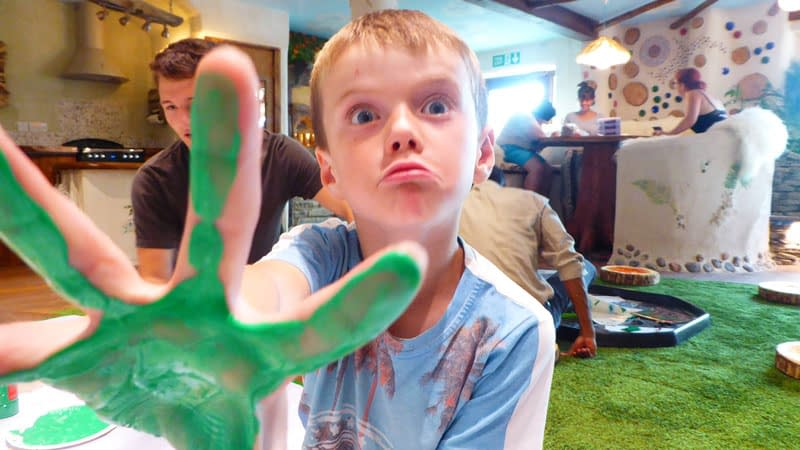 Young boy with green paint on his hands