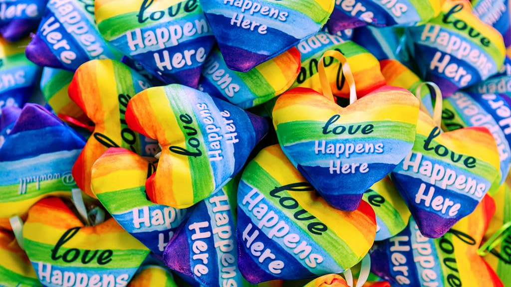 Pile of rainbow cushions with the slogan: love happens here